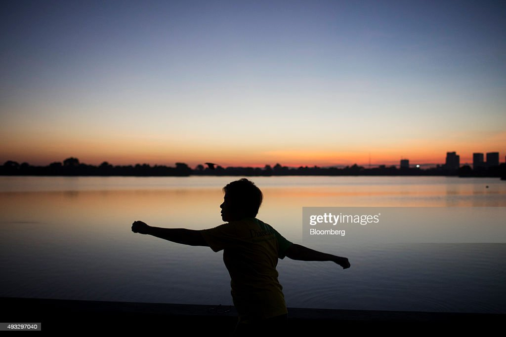 A silhouetted woman exercises at dawn at Inya Lake in Yangon, Myanmar, on Friday, Oct. 16, 2015. Myanmar's government signed a cease-fire agreement with half of the nation's armed ethnic groups, a partial victory for President Thein Sein less than a month before an historic national election. Photographer: Brent Lewin/Bloomberg via Getty Images