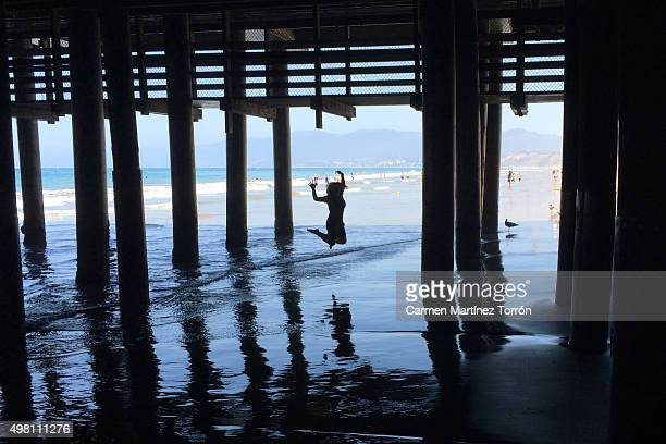 Silhouetted woman jumping under pier, Santa Monica's beach.