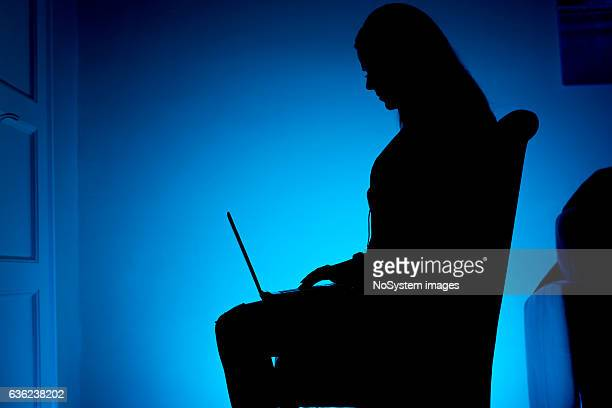 Silhouetted woman, sitting on the chair, working on laptop