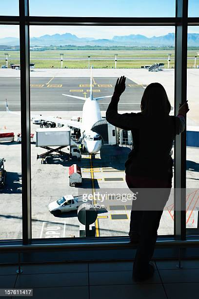 Silhouetted woman waves through airport window at plane