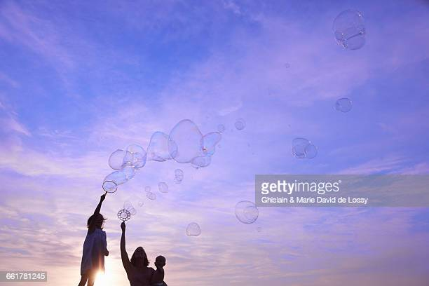 Silhouetted woman with baby son and daughter blowing bubbles against blue sky, Buonconvento, Tuscany, Italy