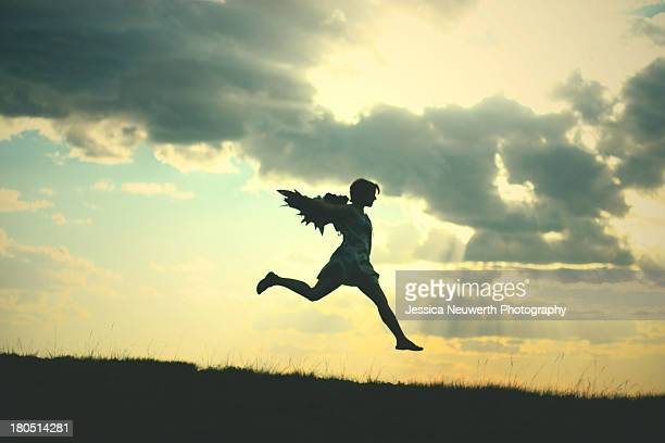 Silhouetted woman with wings leaping again sunset