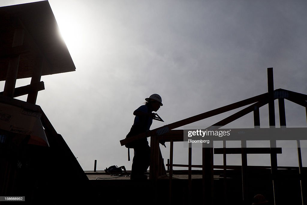 A silhouetted worker builds a house at Davidson Communities LLC's Arista at The Crosby development in Rancho Santa Fe, California, U.S., on Friday, Dec. 21, 2012. New home sales climbed to a 380,000 annual rate in November, the most since April 2010, according to the median forecast of 60 economists surveyed by Bloomberg before Dec. 27 figures from the Commerce Department. Photographer: Sam Hodgson/Bloomberg via Getty Images