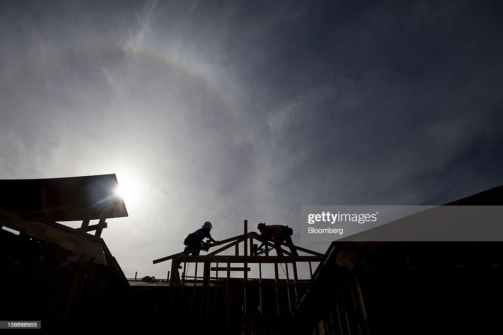 Silhouetted workers build a house at Davidson Communities LLC's Arista at The Crosby development in Rancho Santa Fe, California, U.S., on Friday, Dec. 21, 2012. New home sales climbed to a 380,000 annual rate in November, the most since April 2010, according to the median forecast of 60 economists surveyed by Bloomberg before Dec. 27 figures from the Commerce Department. Photographer: Sam Hodgson/Bloomberg via Getty Images