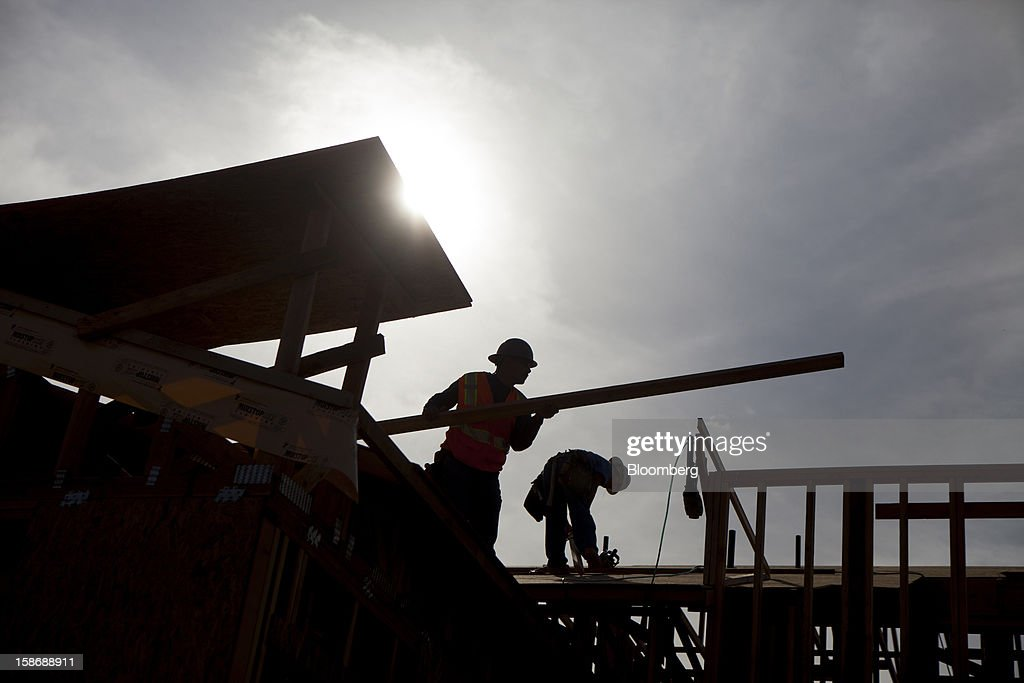 Silhouetted workers build a house Davidson Communities LLC's Arista at The Crosby development in Rancho Santa Fe, California, U.S., on Friday, Dec. 21, 2012. New home sales climbed to a 380,000 annual rate in November, the most since April 2010, according to the median forecast of 60 economists surveyed by Bloomberg before Dec. 27 figures from the Commerce Department. Photographer: Sam Hodgson/Bloomberg via Getty Images