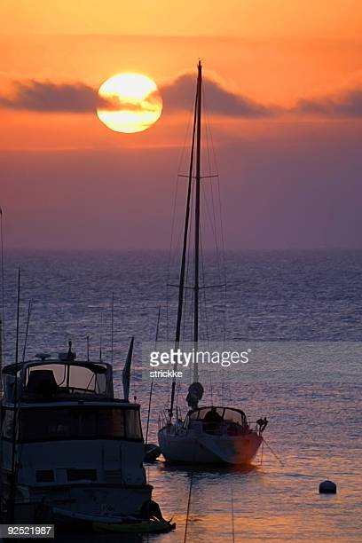 Silhouetted Yachts at Anchor During Vibrant Sunrise or Sunset