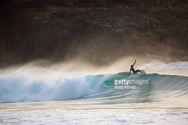 Silhouetted young man surfing wave at sunset, Fuerteventura, Spain