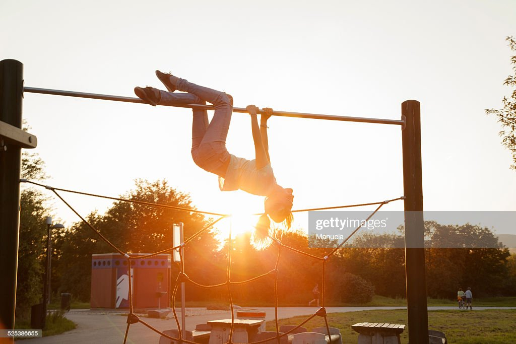 Silhouetted young woman upside down on playground climbing frame at sunset