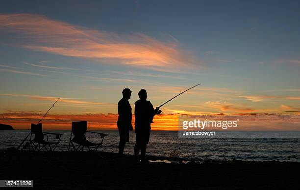 Silhouettes fishing on the beach