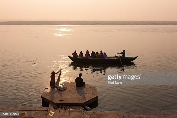 Silhouettes of a boat and pilgrims over the Ganges