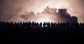 Silhouettes of a crowd standing at blurred military war ship on foggy background. Selective focus. Passengers try to escape. Protest of people
