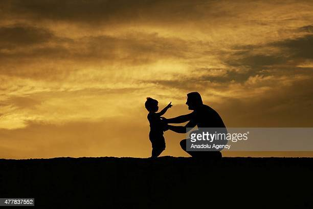 Silhouettes of a man and his son are seen during sunset in Abana district of Kastamonu a province in the Black Sea region of Turkey on June 17 2015