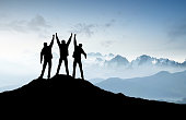 Silhouettes of a team on mountain peak. Sport and active life concept