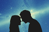 Silhouettes of a young couple under the starry sky. My astronomy work.