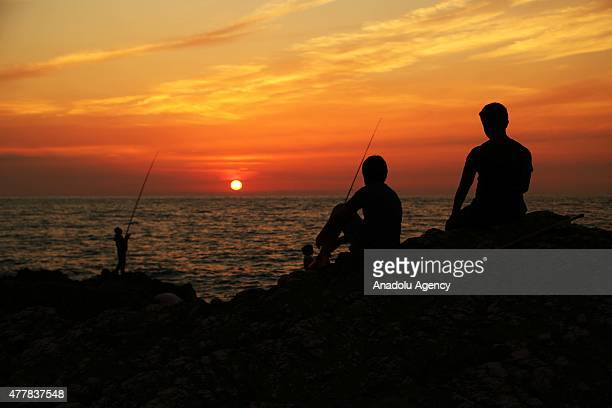 Silhouettes of amateur fishermen are seen during sunset in Abana district of Kastamonu a province in the Black Sea region of Turkey on June 11 2015