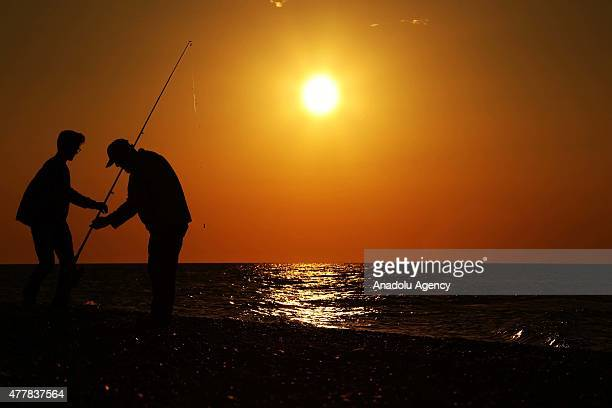 Silhouettes of amateur fishermen are seen during sunset in Abana district of Kastamonu a province in the Black Sea region of Turkey on June 1 2015