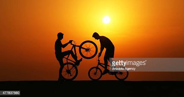 Silhouettes of boys riding bikes are seen during sunset in Abana district of Kastamonu a province in the Black Sea region of Turkey on June 16 2015