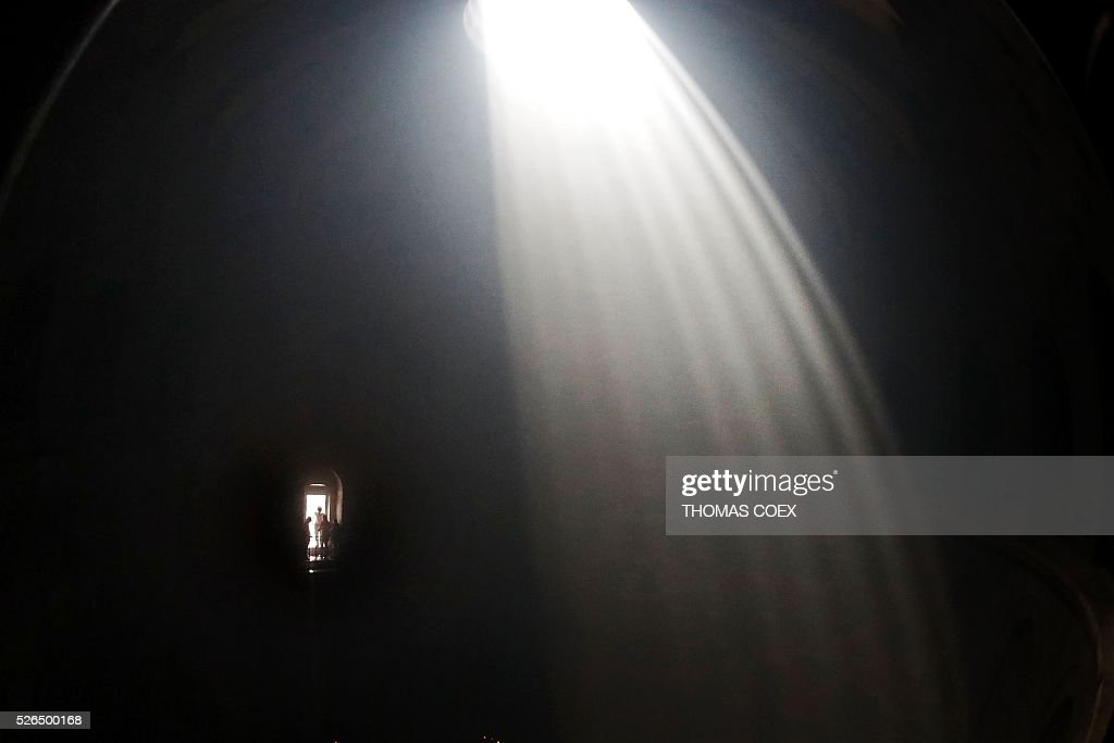 Silhouettes of Christian Orthodox worshippers are seen as a sunbeam shines from the rooftop while thousands gather in the Church of the Holy Sepulchre in Jerusalem's Old City, on April 30, 2016, during the Orthodox Easter ceremony of the 'Holy Fire'. The ceremony celebrated in the same way for eleven centuries, is marked by the appearance of 'sacred fire' in the two cavities on either side of the Holy Sepulchre. / AFP / THOMAS