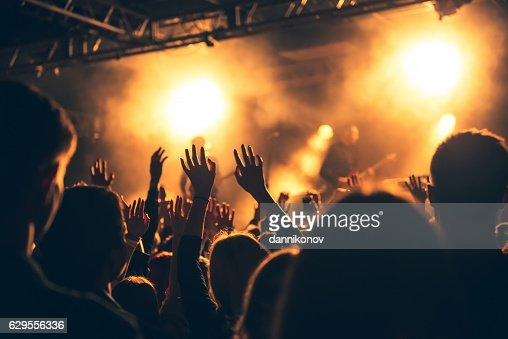silhouettes of concert crowd in front of bright stage lights : Stock Photo