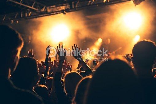 Siluetas de concert crowd in front of amplia luces de escenario : Foto de stock
