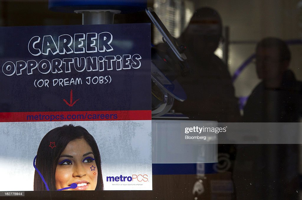Silhouettes of customers browsing phones are seen past a sign advertising career opportunities in the window of a MetroPCS Communications Inc. store in San Francisco, California, U.S., on Tuesday, Feb. 26, 2013. MetroPCS Communications Inc. fourth-quarter revenue, released today, matches estimated earnings. Photographer: David Paul Morris/Bloomberg via Getty Images