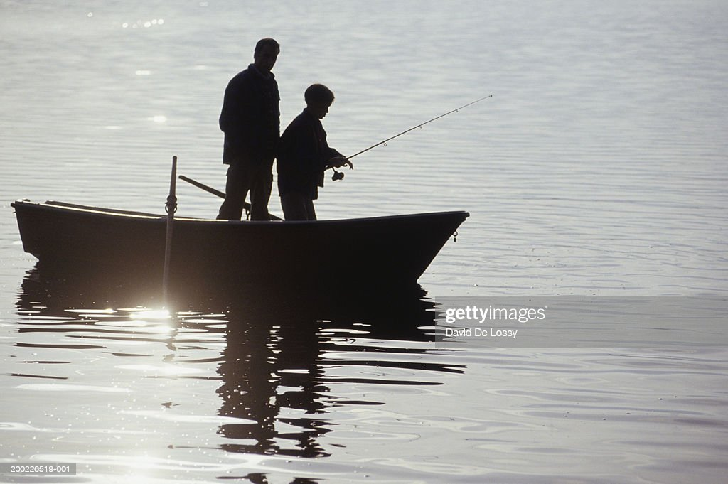 Silhouettes of father and son standing in boat fishing for Father son fishing