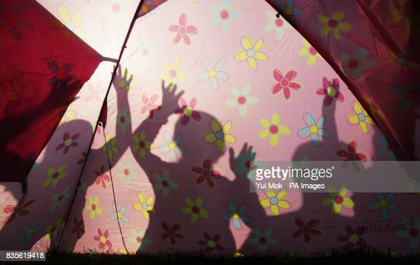 Silhouettes of festival goers in a camping area on the day before the Glastonbury Festival starts at Worthy Farm in Somerset