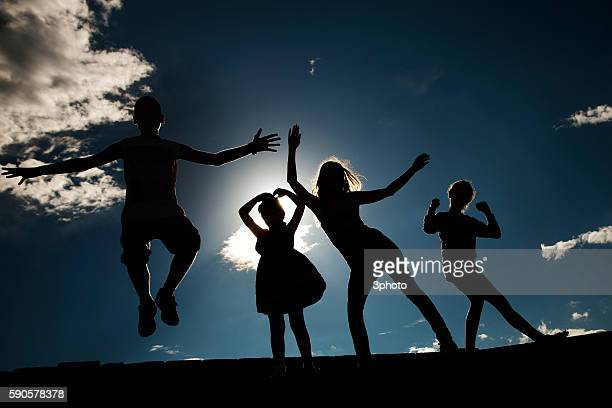 Silhouettes of four people against the sky