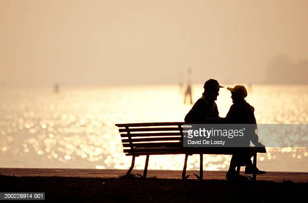 Silhouettes of man and boy (12-13years) sitting on bench by sea in sunset, rear view