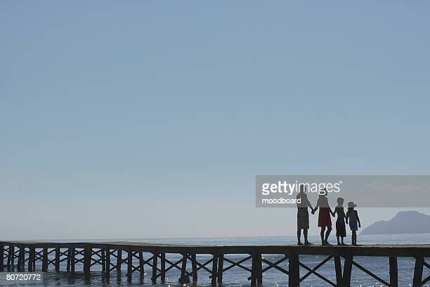 Silhouettes of parents and children (6-11) on jetty