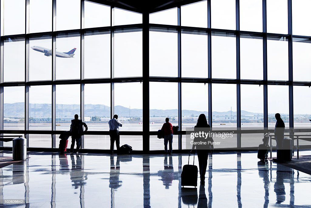Silhouettes of passengers waiting at an airport