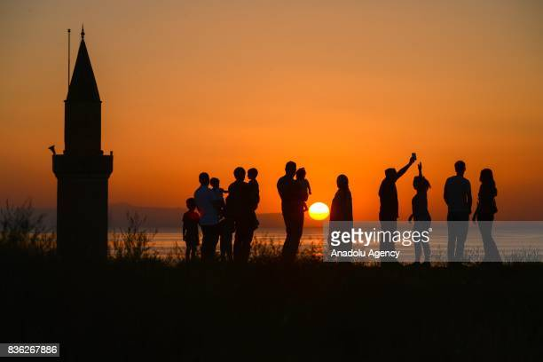 Silhouettes of people are seen during a sunset over Van Lake on August 21 2017 in Van Turkey