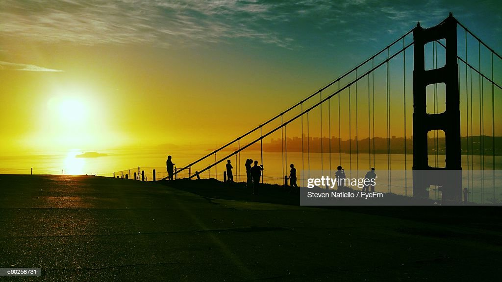 Silhouettes Of People By Suspension Bridge