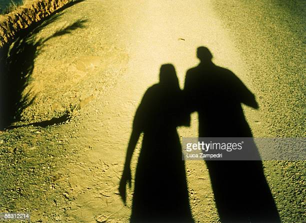 Silhouettes of people on dirt road