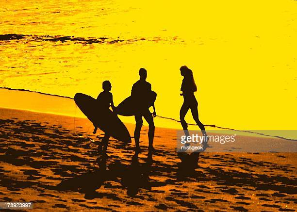 Silhouettes of people on the beach at sunrise