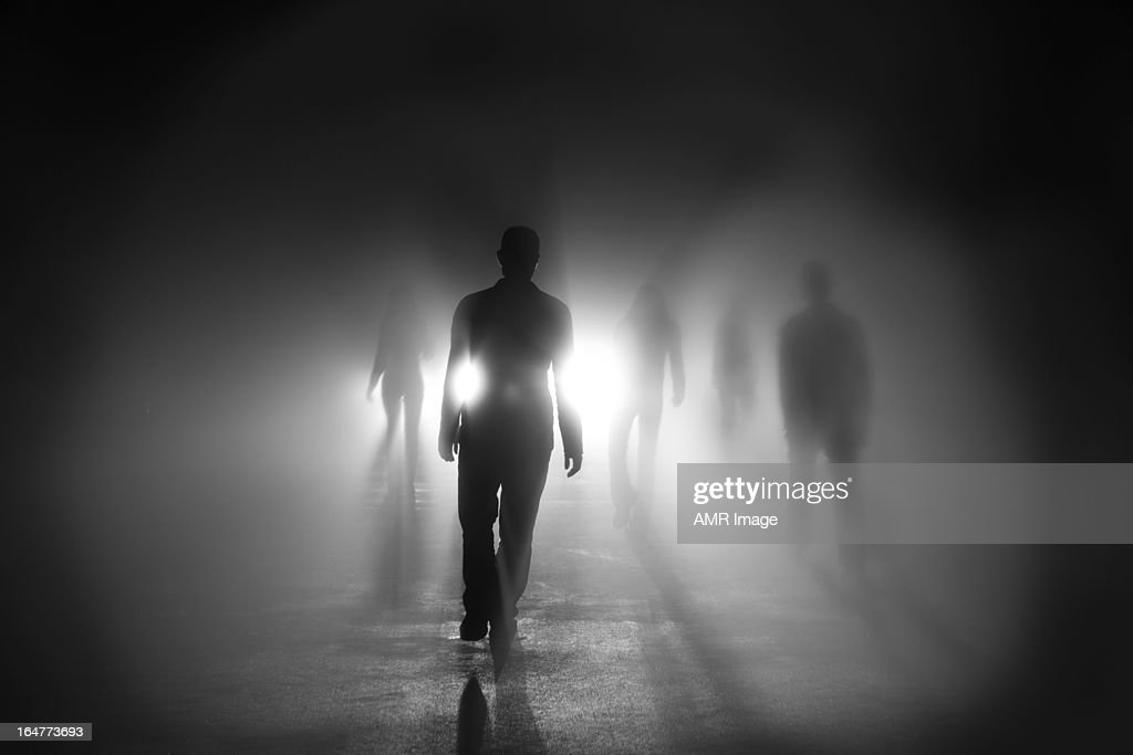 Silhouettes of people walking into light : Stock Photo