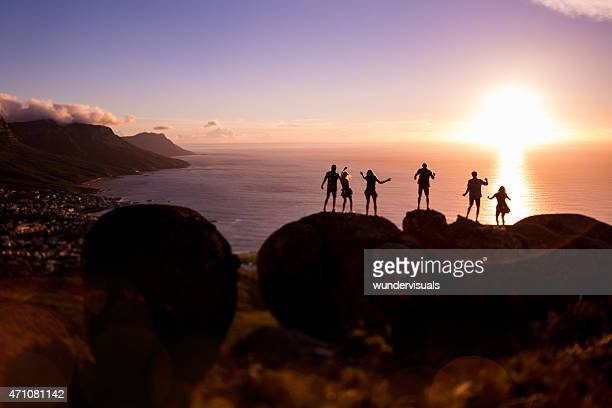 Silhouettes of people with the sun setting over the ocean
