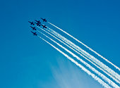 Silhouettes of seven fighter planes with smoke in airshow