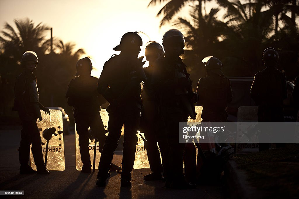 Silhouettes of soldiers are seen blocking access to the Windsor Barra Hotel in Rio de Janeiro, Brazil, on Monday, Oct. 21, 2013. Soldiers, army vehicles, helicopters and navy ships are guarding a Rio de Janeiro hotel where companies including China National Petroleum Corp., Royal Dutch Shell Plc and Total SA are expected to vie for one of the worlds two largest offshore fields at 3 p.m. local time, as oil workers protest the concession. Photographer: Dado Galdieri/Bloomberg via Getty Images