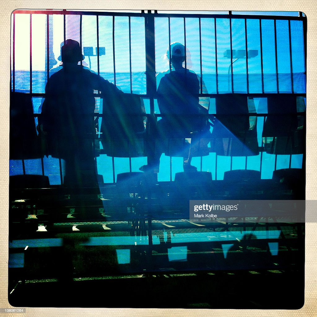 Silhouettes of supporters in the grandstand watch the action on an outside court during day seven of the 2012 Australian Open at Melbourne Park on January 20, 2012 in Melbourne, Australia.