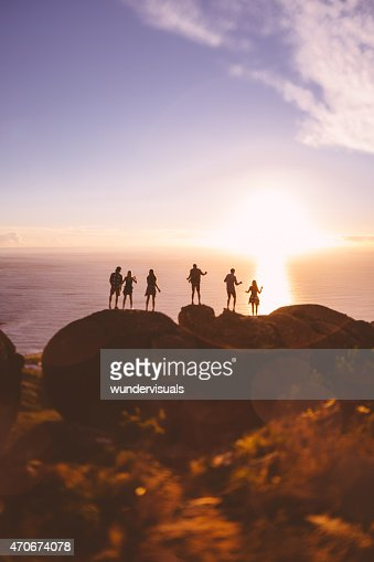 Silhouettes of teens on rocks with sunset over the sea