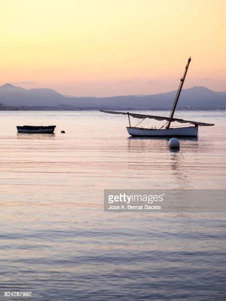 Silhouettes of three wooden fishing boats near the beach during an orange sunset on the island of Tabarca, Spain