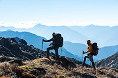 Silhouettes of two Hikers staying on rocky and grassy Ridge with Backpacks and other Gear expressing Energy and Happiness. Layered Mountain Valley View on Background