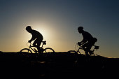 Silhouettes of two mountain bikers, Slickrock, Utah, USA