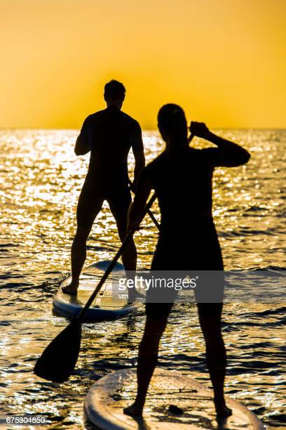Silhouettes of two people rowing toward the sun