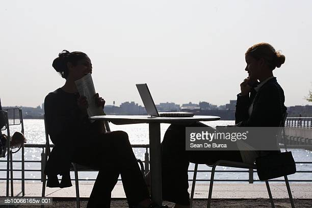 Silhouettes of two women in outdoor cafe, one using laptop