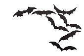 Silhouettes of volatile bats carved out of black paper are isolated on white for Halloween festival