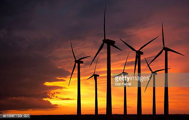 Silhouettes of wind turbines against sunset sky