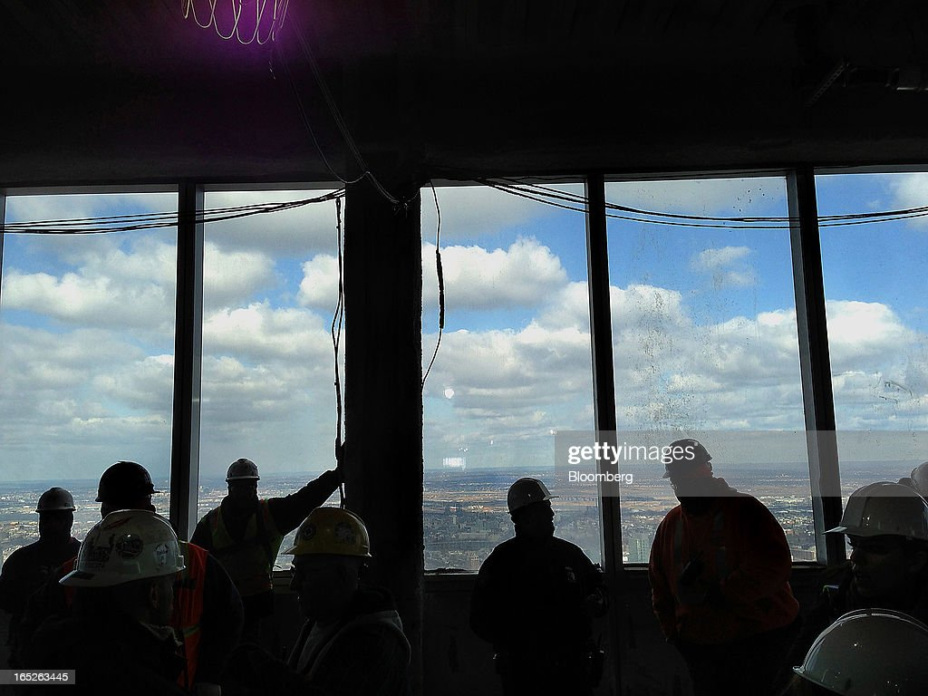 Silhouettes of workers are seen during a tour of the One World Trade Center observation deck in New York, U.S., on Tuesday, April 2, 2013. The observation deck at One World Trade Center, expected to open in 2015, will occupy the tower's 100th through 102nd floors. Guests visiting the observation deck will see a 'pre-show' about the creation of the building while waiting in line in the lobby. Photographer: Victor J. Blue/Bloomberg via Getty Images