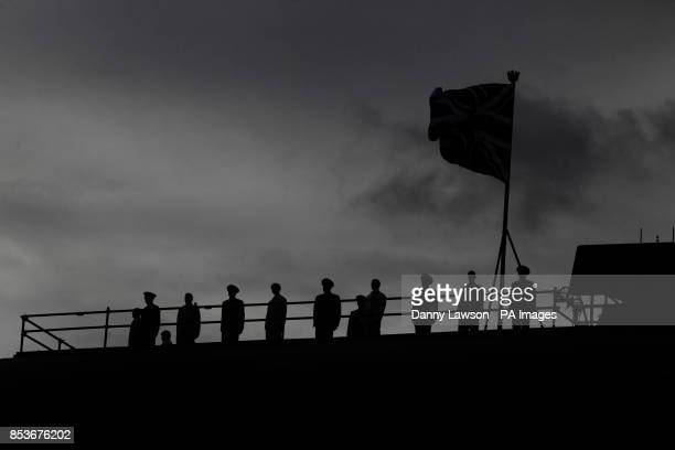 Silhouettes on deck as Queen Elizabeth II officially named Royal Navy's new aircraft carrier HMS Queen Elizabeth during a visit to Rosyth dockyard in...